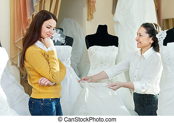 saleswoman helps girl chooses white bridal gown - Mature...