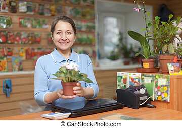 saleswoman with flower at garden store