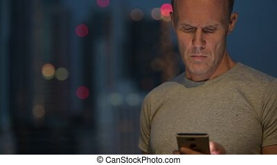 Mature Scandinavian man thinking while using phone against view of the city
