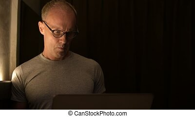 Mature Scandinavian man using laptop with eyeglasses
