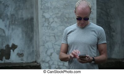 Mature Scandinavian man using phone with sunglasses