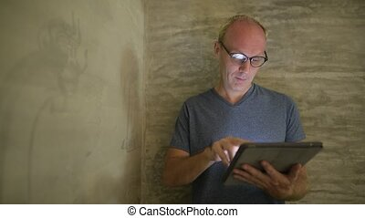 Mature Scandinavian man video calling with digital tablet at home