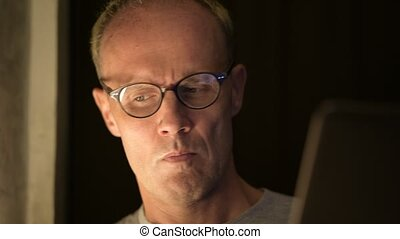 Mature Scandinavian man with eyeglasses thinking while using laptop