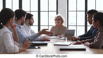 Front view mature senior businesswoman ceo boss sitting at table with mixed race young employees, brainstorming on project ideas, developing marketing growth strategy, discussing working issues.