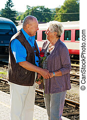 mature senior couple at the train station