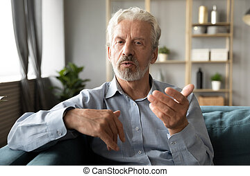 Mature senior grandfather chatting with friends family via ...