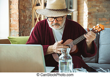 Playing on ukulele, guitar. Senior man during quarantine, realizing how important stay at home during virus outbreak. Concept of lockdown of coronavirus, self-insulation, healthcare, safety, protection.
