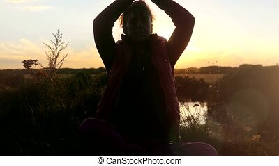 Mature slim woman sitting on the cliff and raising her hands doing yoga enjoying a sunset or sunrise.