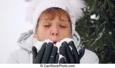 Mature smiles woman in age blowing snowflakes in slowmotion in the park in winter. 1920x1080