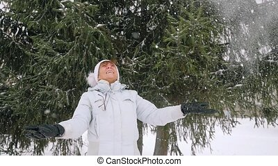 Mature smiles woman in age throwing snowflakes in slowmotion in the park in winter.