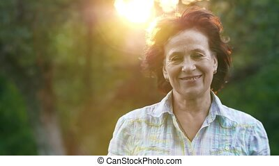 Mature smiling woman on sunset