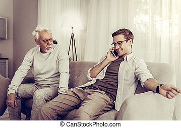 Mature son talking over phone while father sitting on a couch