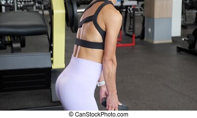 Mature sportive woman is doing deadlift in the gym holding ...