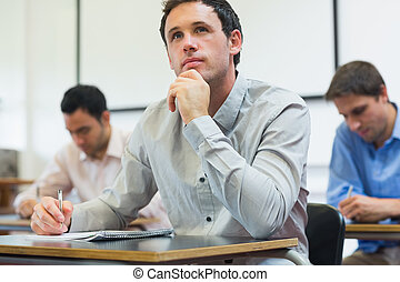 Mature students taking notes in classroom - Thoughtful...