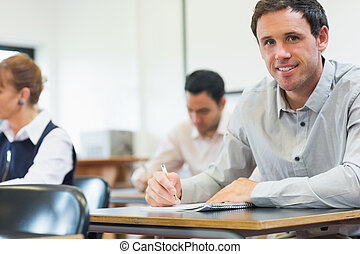 Mature students taking notes in classroom - Portrait of a...