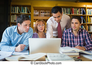 Mature students with teacher and laptop in library - Mature ...