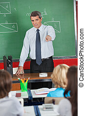 Mature Teacher Pointing At Students