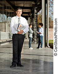 Mature Teacher With Books Standing On University Campus -...