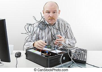 Mature Technician Repairing Computer At Desk