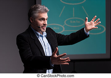 Mature trainer gesturing before screen with presentation. ...