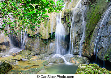 Jungle waterfall cascade Thac Voi at tropical rainforest in Thanh Hoa province, Vietnam. Current stream gushing through cascade tiers into emerald pond with by mature trees
