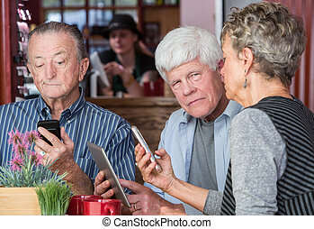 Mature Trio in Coffee House Using Electronic Devices
