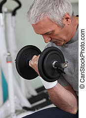 mature white-haired man lifting weight in sports room