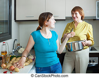 Mature woman and adult daughter cooking food