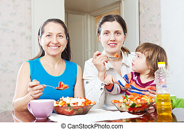 Mature woman and adult daughter with baby eats vegetables