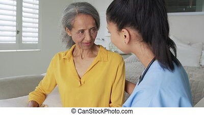 Front view close up of a mature mixed race woman talking with a young mixed race female nurse comforting her while sitting on a bed
