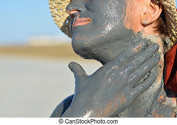 Mature woman applying mud on face and hands outdoors