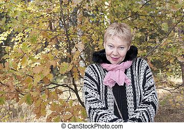 Mature woman at autumn oak