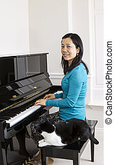 Mature woman at piano with her cat