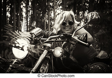 Mature woman biker on a motorcycle in sepia