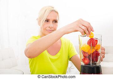 Mature woman blending a smoothie