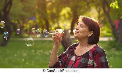 Mature woman blowing bubbles