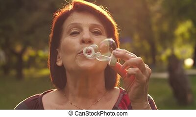 Mature woman blowing soap bubbles - Elderly woman blowing...