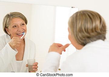 Mature woman brushing teeth look bathroom mirror