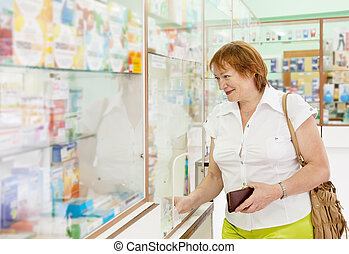 woman buys drugs at the pharmacy