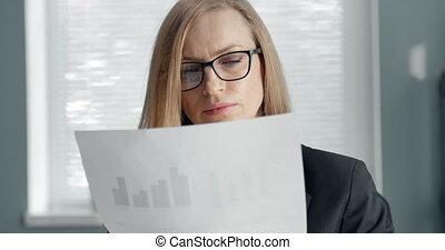 Mature woman carefully reading important document - Portrait...