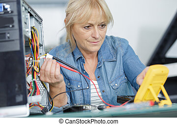 mature woman checking the currect of a pc