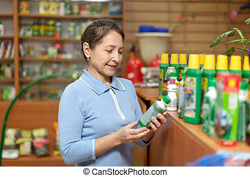 mature woman chooses agricultural chemistry at garden shop