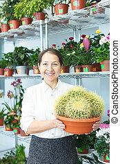 mature woman chooses cactus
