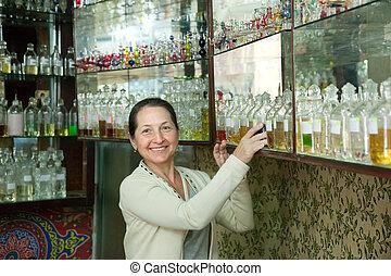Mature woman chooses essential oils at shop