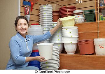 Mature woman  chooses flowerpot