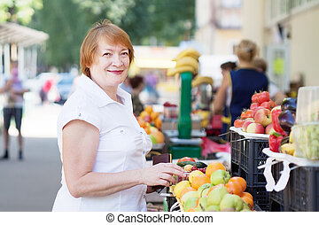 Mature woman chooses fruits