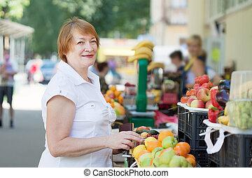 Mature woman chooses fruits