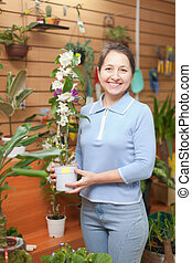 Mature woman chooses  orchid