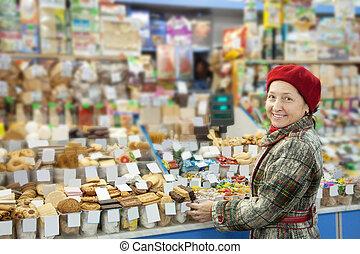 Mature woman chooses sweets