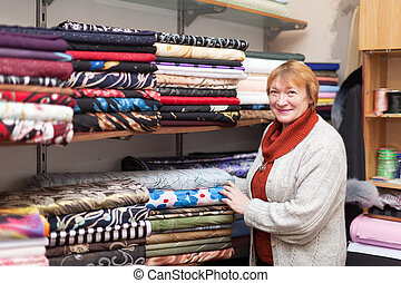 woman chooses tissue at fabric store - Mature woman chooses...